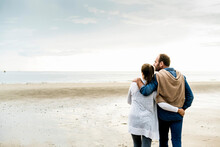Couple With Arms Around Looking At Sea Against Cloudy Sky During Weekend