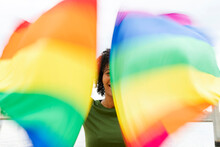 Close-up Of Mid Adult Woman Waving Rainbow Flags While Standing In City