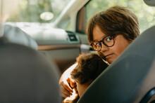 Boy Sitting With Puppy In Car