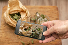 Hand Holding Smart Phone While Photographing Dried Linden Leaves In Paper Bag And Glass Of Lime Tea On Wooden Cutting Board