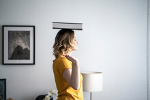 Woman At Home Balancing A Book On Her Head