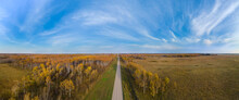 Aerial Panoramic View Of High Above A Gravel Road Running Between Autumn Colored Trees Under A Dramatic Blue Sky With White Clouds.