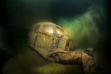 Underwater View Of Rusty Car Wreck Deteriorating At Bottom Of Lake Atter