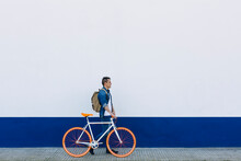 Man With Bicycle Walking On Footpath