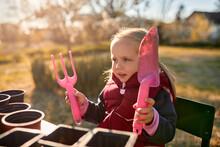 Portrait Of Girl Holding Gardening Tools