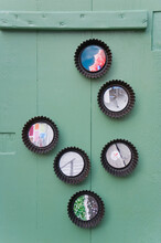 Photos In Upcycled Baking Dishes Hanging On A Green Wooden Wall