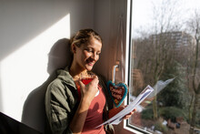 Smiling Young Woman Reading Paper At The Window