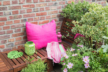 Balcony With Bench, Pink Cushion, Blanket, Lanterns And Various Potted Plants