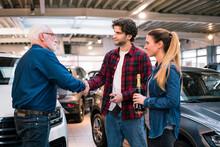 Couple Buying New Car At Car Dealership
