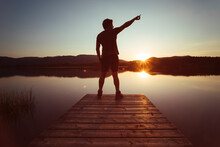 Silhouette Of A Man Pointing To The Sky On A Wooden Walkway At Sunset