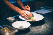 Cook Serving Food On A Plate In The Kitchen Of A Restaurant