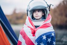 Portrait Of Little Boy Wrapped In American Flag Wearing Space Helmet