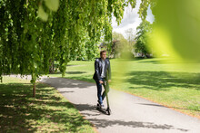 Businessman Using E-Scooter In A Park