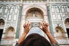 Close-up Of Young Woman Taking A Smartphone Picture In The City, Florence, Italy