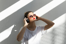 Portrait Of Young Woman With Red Lips Listening Music With Headphones