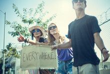 Young Friends Hitchhiking While Holding Placard With Written Text