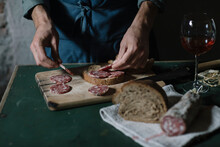 Midsection Of Young Man Preparing Salami Sandwich On Cutting Board At Table