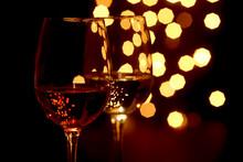 Germany,ÔøΩGlasses Of Wine WithÔøΩChristmas LightsÔøΩin Background