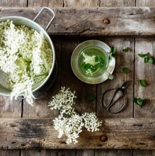 Saucepan With Fresh Elderflowers And Cup Of Elderflower Tea With Mint