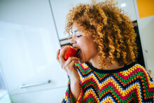 Young Woman With Curly Hair Eating An Apple In Kitchen
