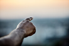 Cropped Hand Of Man Pointing At Sky From Building Terrace During Sunset
