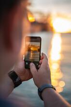 Germany,ÔøΩHamburg, Hands Of Man Taking Smart Phone Photos Of Port Of Hamburg At Sunset