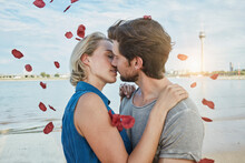 Germany, Duesseldorf, Affectionate Young Couple Kissing At Rhine Riverbank Surrounded By Falling Rose Petals