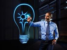 Businessman Painting Lightbulb With A Sun Inside