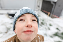 Boy Looking Up On Falling Snow