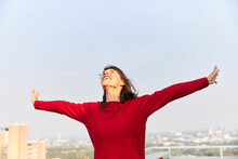 Mature Woman With Arms Outstretched Standing On Building Terrace