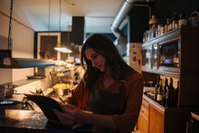 Young Woman In Restaurant Kitchen Writing Into Book