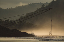 Indonesia, Sumbawa Island, Man And Construction Crane At Seaside