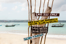 Indonesia, Bali, Jimbaran, Sign With Motivational Quotes Standing On Coastal Beach