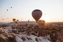 Hot Air Balloons Flying Over Rocky Landscape Against Clear Sky In Goreme During Sunset, Cappadocia, Turkey