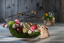 Easter Eggs In Wire Basket With Easter Bunny In The Foreground