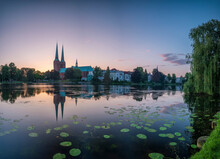 Germany, Schleswig-Holstein, Lubeck, Water Lilies Growing On Bank Of Trave At Dusk With Old Town Buildings In Background