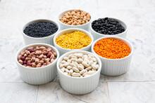 Various Legumes In Bowls: Chickpeas, Cannellini Beans, Quail Beans, Black Beans, Yellow Lentils, Red Lentils, Black Lentils