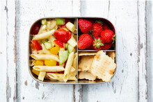 Pasta Salad, Strawberries And Crackers In Lunch Box On Wooden Table