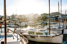 Spain, Mallorca, Port De Pollenca, Sun Shining Over Sailboats Moored In Harbor