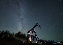 Pumpjack Against Starry Sky With Milky Way In Natural Mountains Environment For Mining Gasoline, Pipeline System Extract Crude Oil Petroleum And Water Emulsion At Each Stroke During Night Time