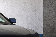 Shot Of A Front Glass Window Of A Black Car And The Side Left Mirror Parked Near The Wall