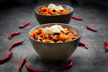 Red Chili Peppers And Two Bowls Of Vegetarian Chili With Red Lentils, Kidney Beans, Tomatoes, Carrots, Celery And Sour Cream