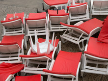 Heap Of White Plastic Chaise Lounge With Red Mattresses On Sea Side Cement Beach Top View