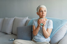 Shot Of A Senior Woman Enjoying A Relaxing Coffee Break On The Sofa At Home. Happy Mature Woman With Coffee Cup Relaxing By The Window. Coffee And A Quiet Moment