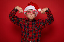 Adorable Preteen Boy In Santa Claus Hat And Plaid Shirt Looks At Camera Through Christmas Sweet Candy Canes, Holding Them Imitating Eyeglasses, Posing On Red Background With Copy Space For Ad