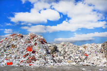 Photo Of A Large Amount Of Garbage And Rubbish At The Dump In The Street Under The Blue Sky With White Clouds