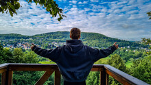 Man With Arms Stretched Out In Front Of Landscape