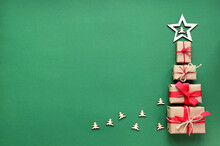 Christmas Tree Made From Wrapped Gift Boxes With Red Ribbons With A Wooden Star On A Green Background.