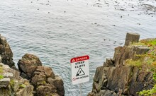 Sign Warning Of Steep Cliffs And Danger On The Rocky Ocean Shore