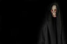 Human Skull In Black Hood In The Dark
